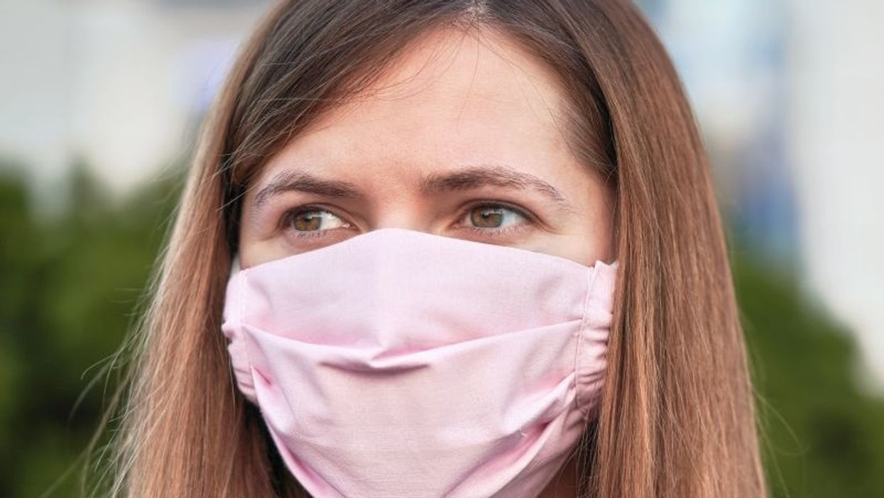 brunette woman wearing pink face mask outdoors
