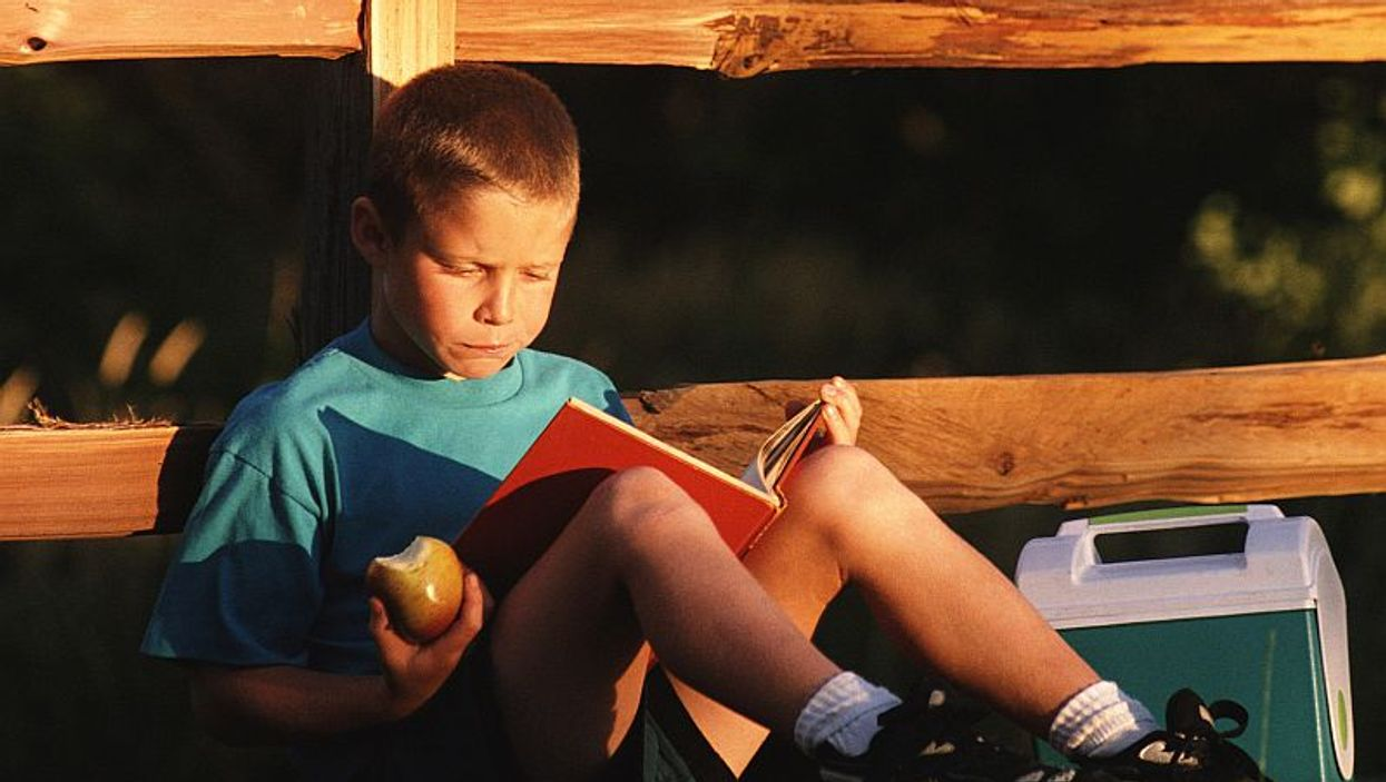 boy reading a book outside