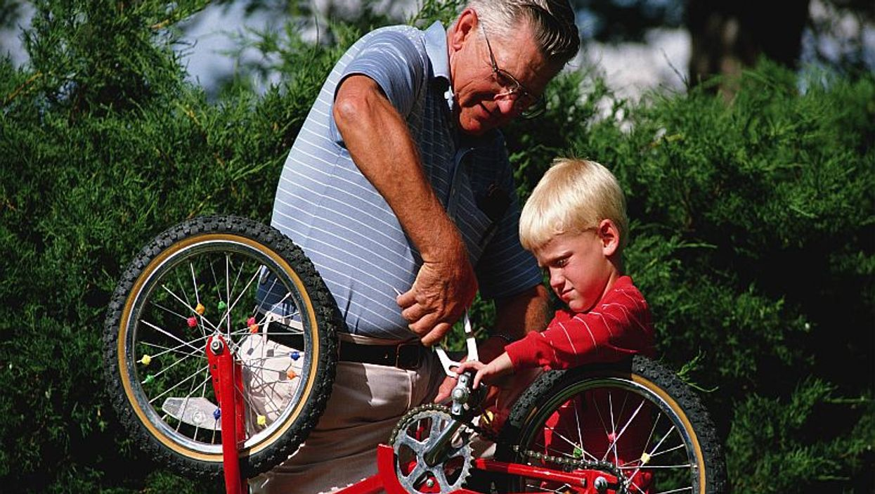 man fixing a bike with a boy