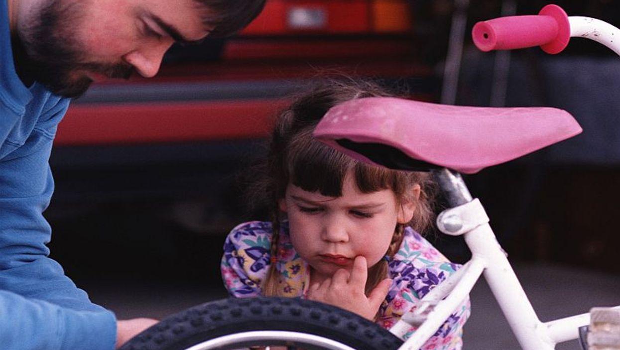 parent fixing girl bike