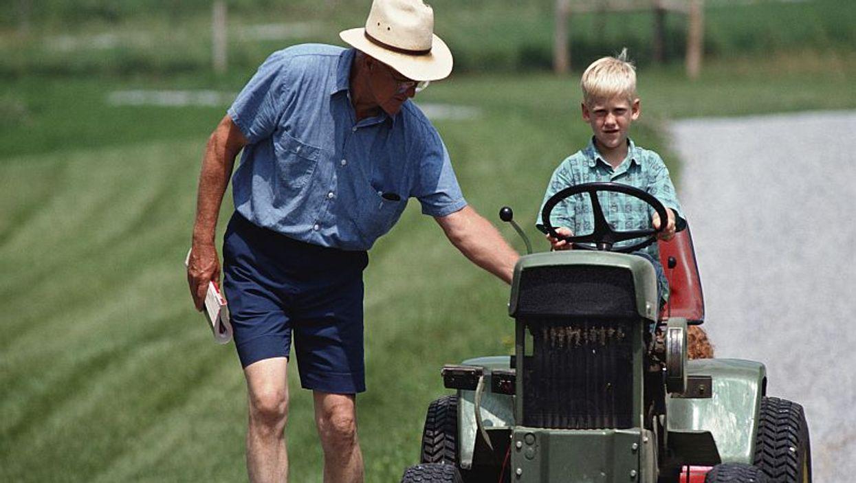 man teaching a boy to ride on a lawn mower