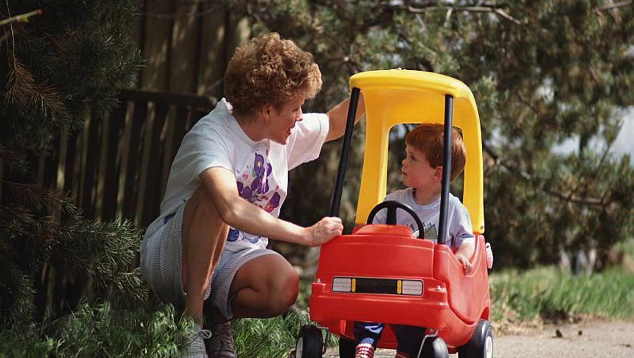 kid in a toy car with a caregiver