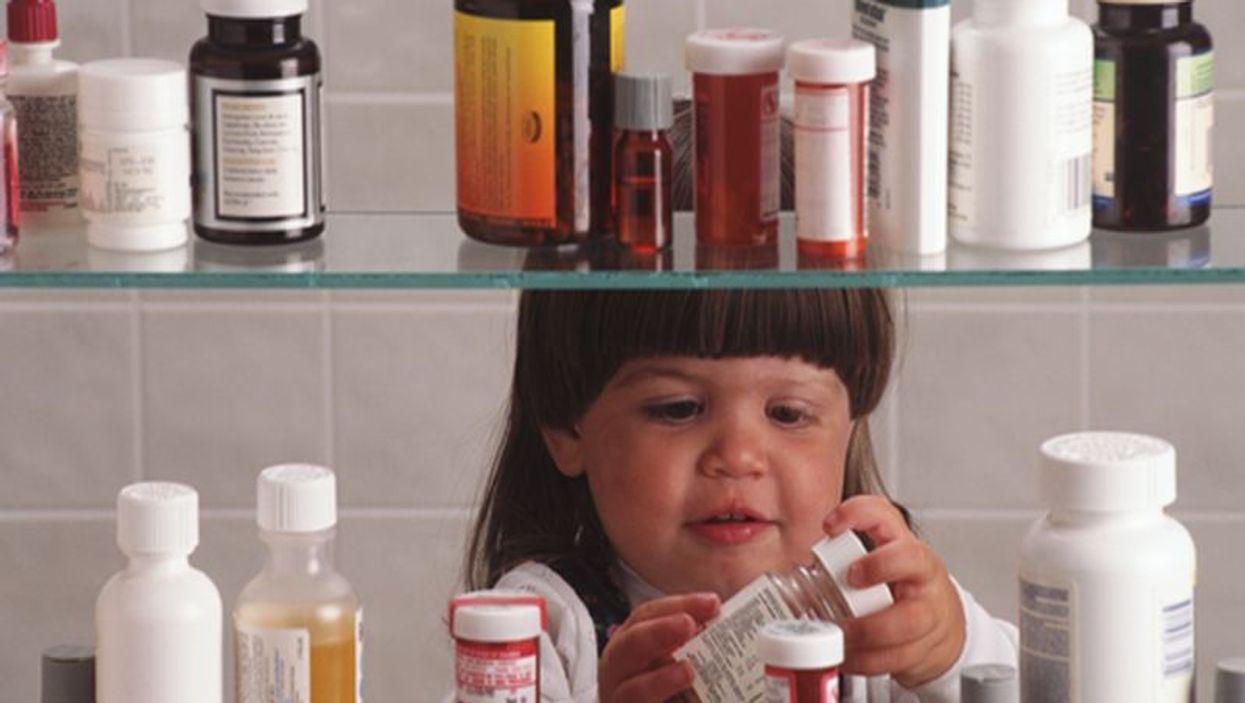 little girl checking a medicine cabinet