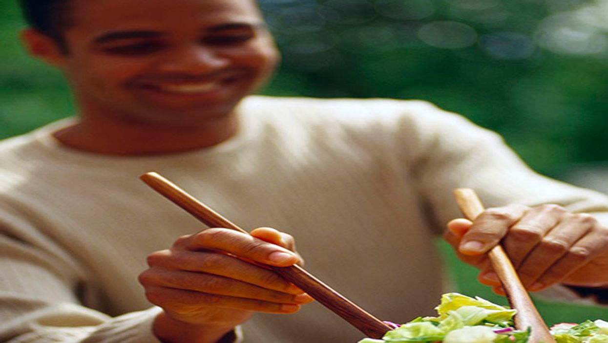 man serving salad from a bowl