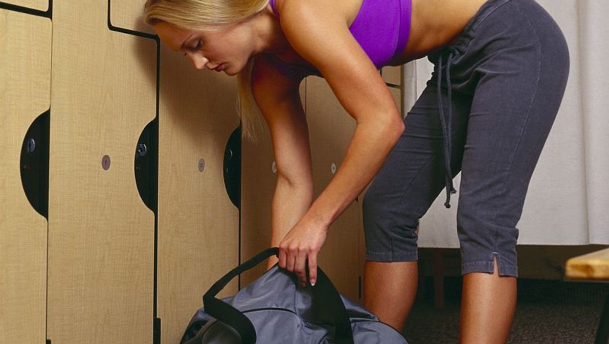 woman packing her bag in a gym locker
