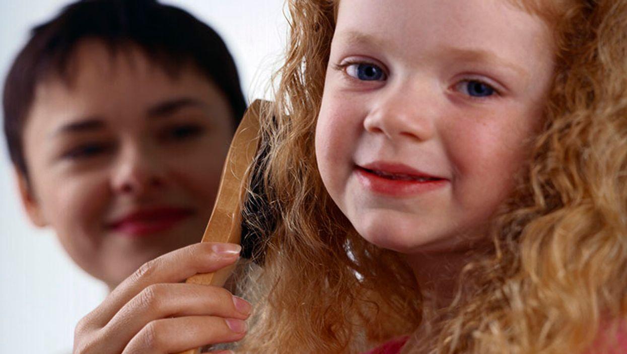 mother brushing daughter\'s hair