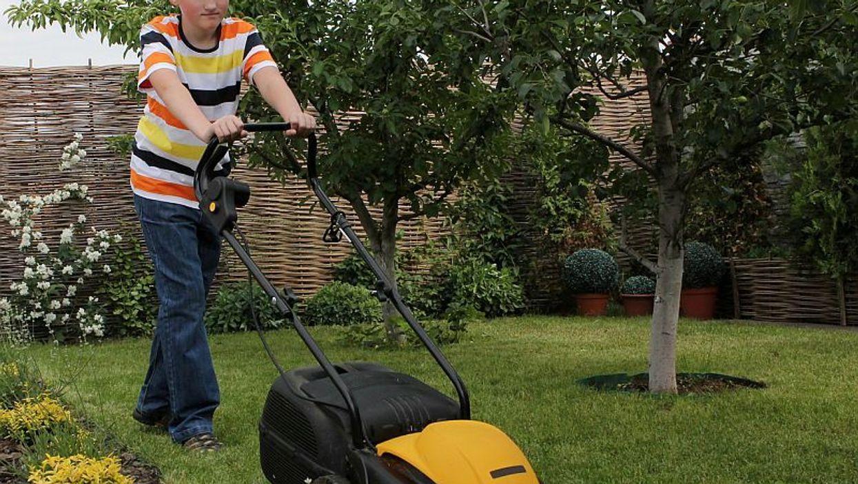 teen boy mowing lawn