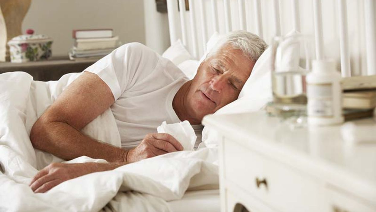 man lying in a bed looking sick