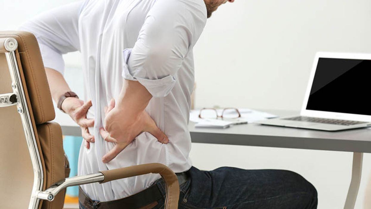 man holding his back in pain at the desk