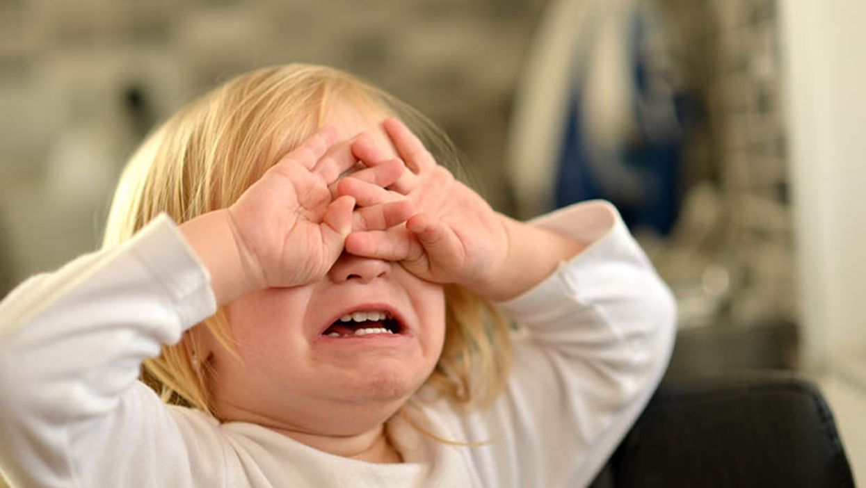 small child crying covering his eyes