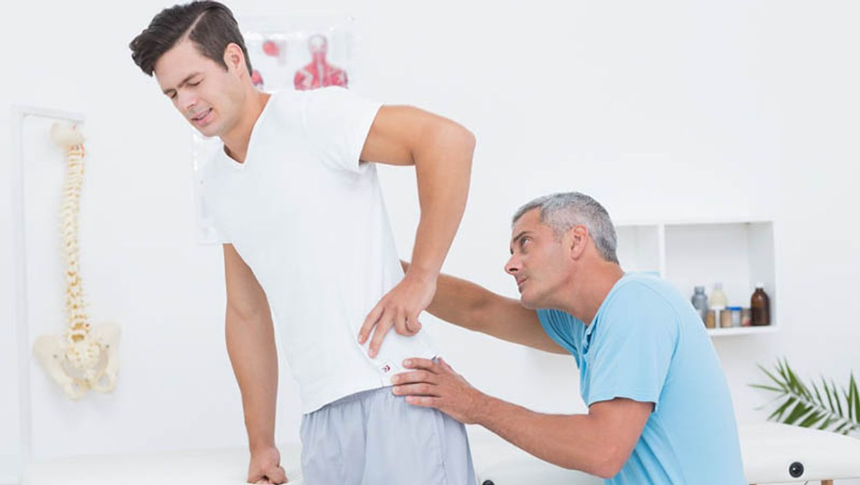 Patient with backache being examined