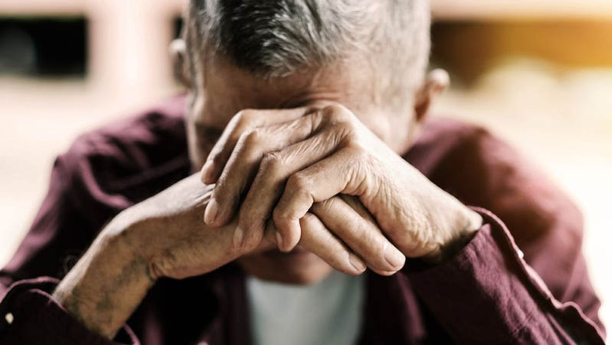 depressed man with hands over his face