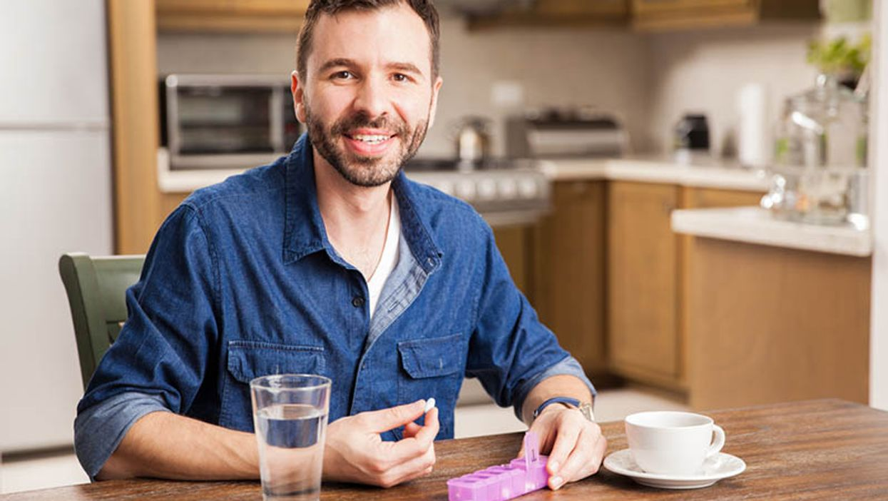 man taking his pill and smiling