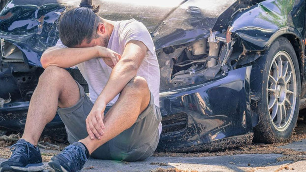 a man sitting on the ground in front of the crashed car