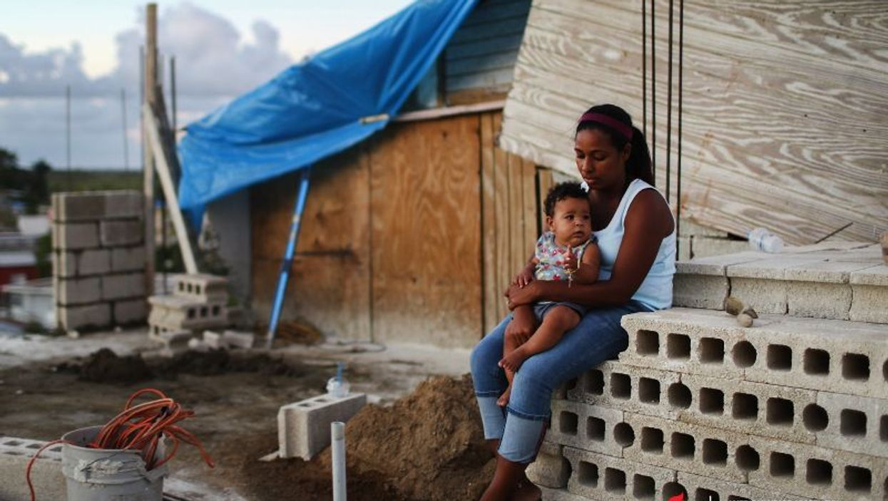 A mother holds her 9-month-old 3 months after Hurricane Maria destroyed her home in Puerto Rico