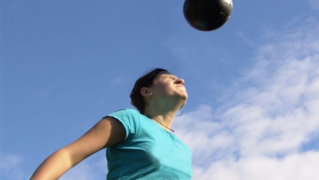 female heading soccer ball