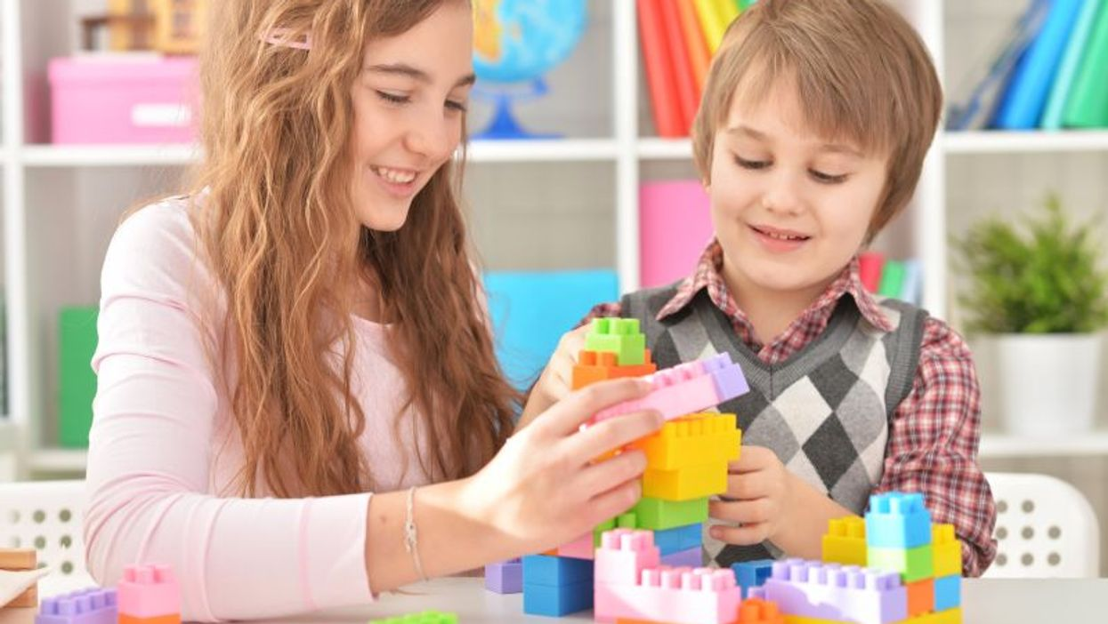 a boy and a girl playing with lego blocks