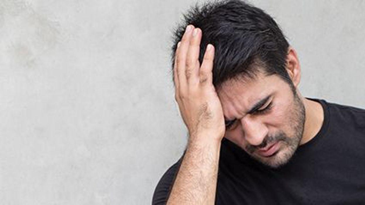 a man with a headache holding his head