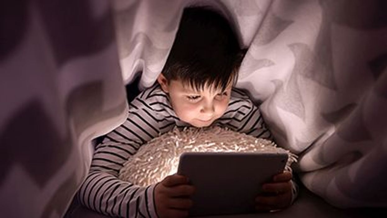 a boy in a bed with his ipad