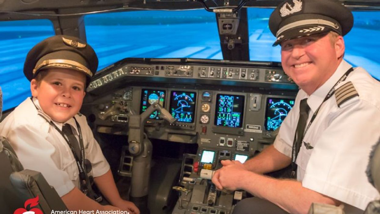 Easton Fryer in a flight simulator with Ric Wilson, vice president of flight operations for Envoy Air.
