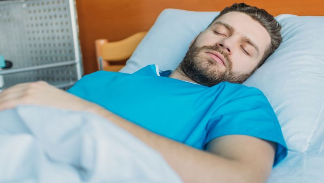 man sleeping in hospital bed