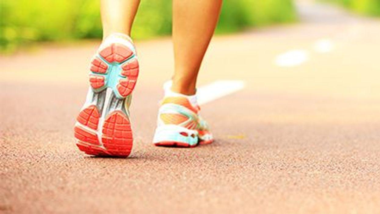 a person\'s feet walking wearing sneakers