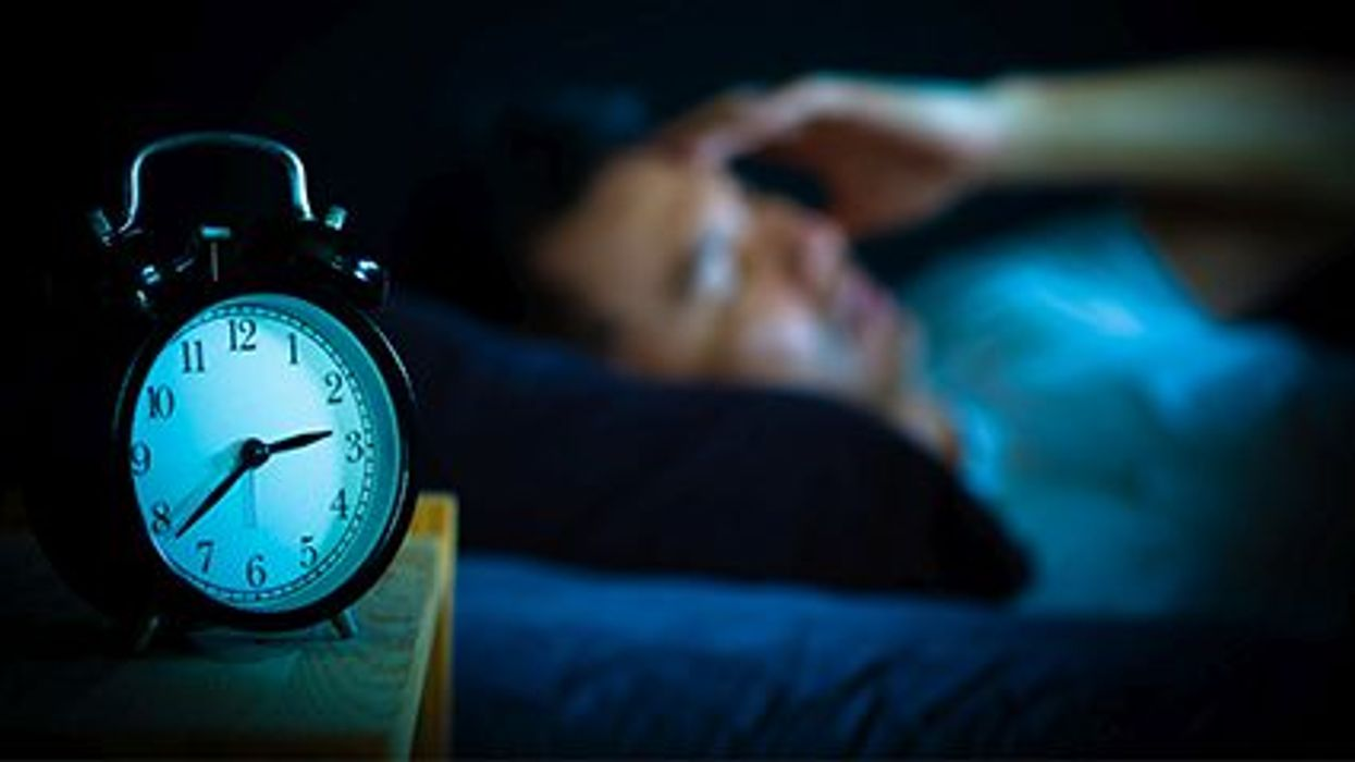 a person awake during night lying in a bed