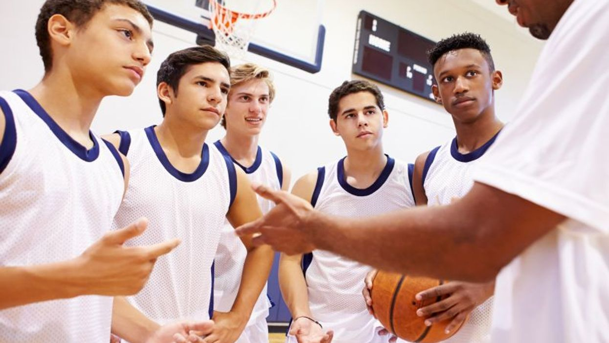 Basketball coach talks with players
