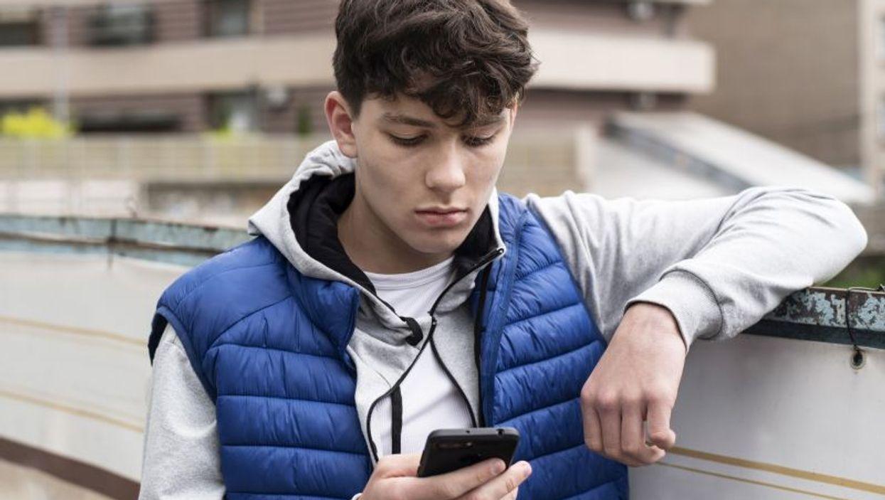 sad teen boy texting