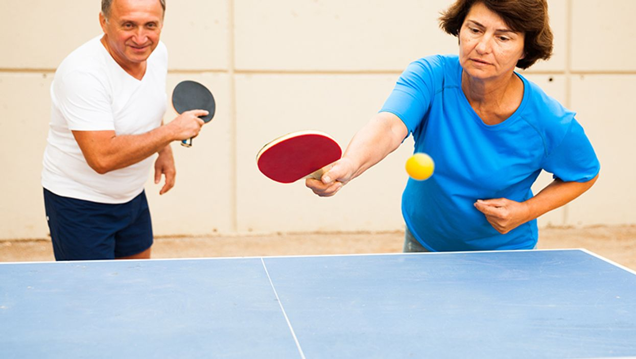 happy adults playing table ping pong