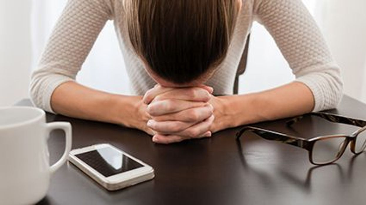stressed woman at the desk with her head down