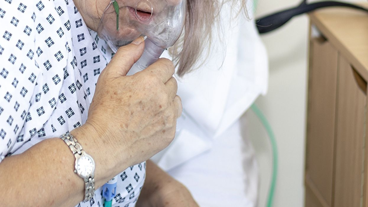 Woman in hospital with breathing difficulties using a respiration mask