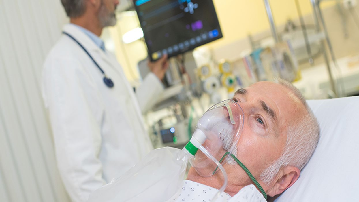 doctor examining his patient wearing oxygen mask