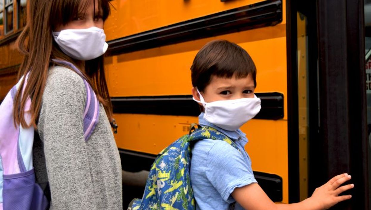 child wearing mask boarding school bus