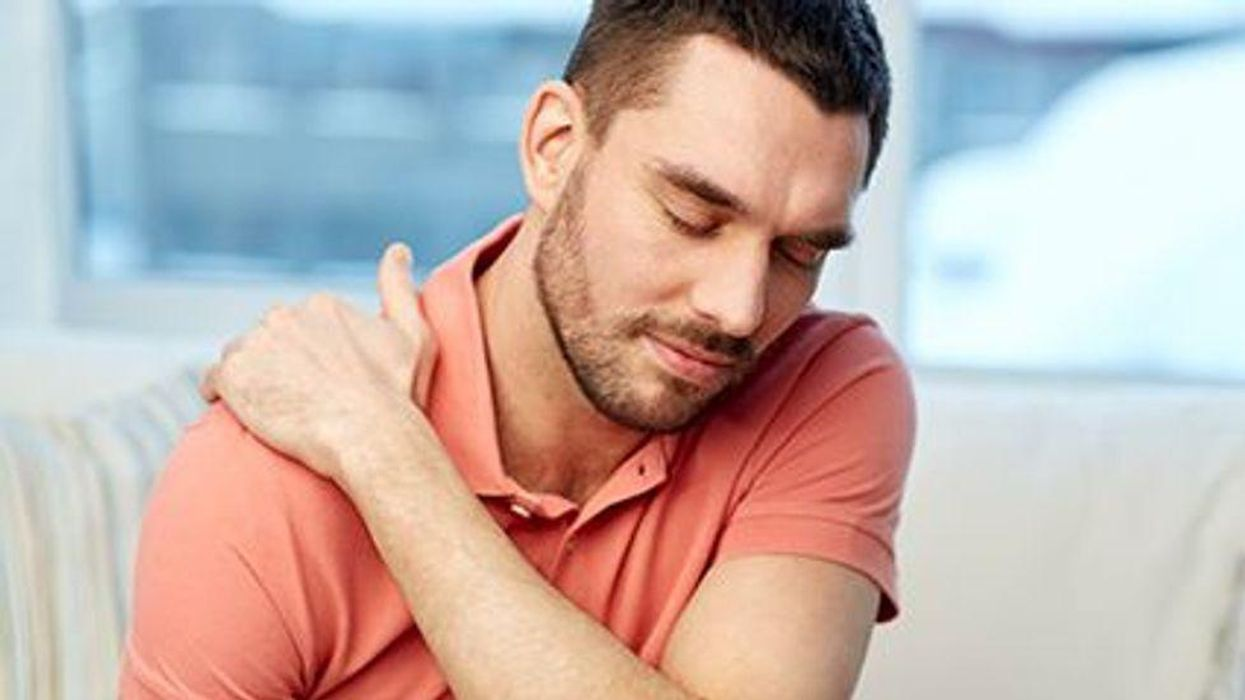 a man holding his shoulder in pain
