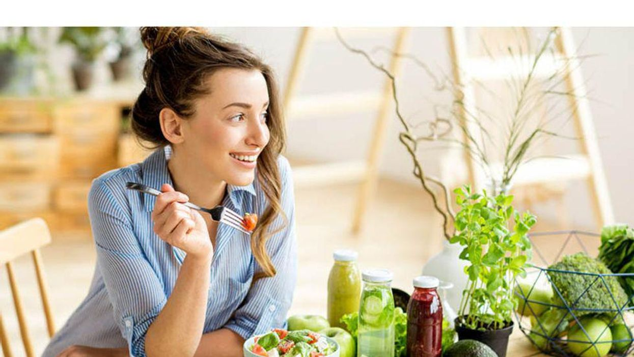 woman smiling and eating a healthy salad