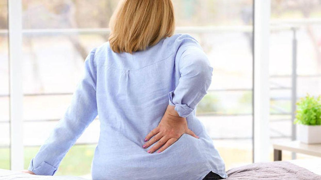 woman holding her back in pain