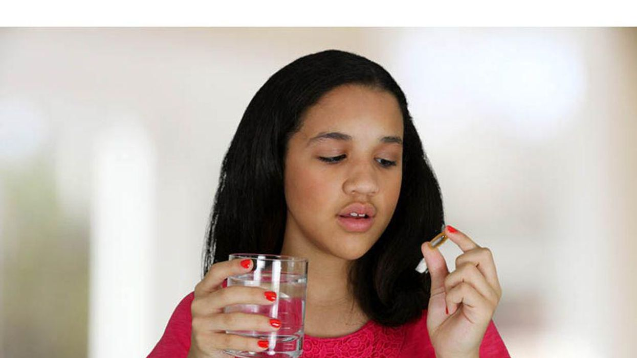 a girl ready to swallow her pill with glass of water