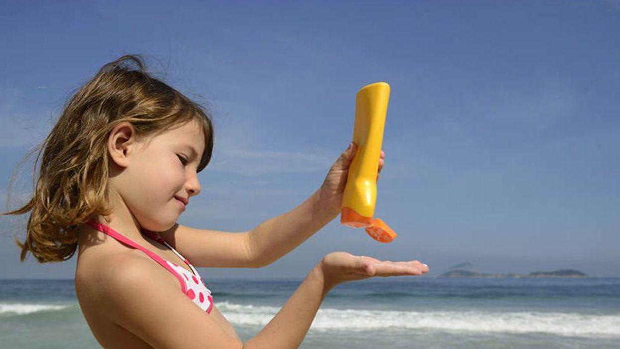 a little girl on the beach spreading sunblock on her skin
