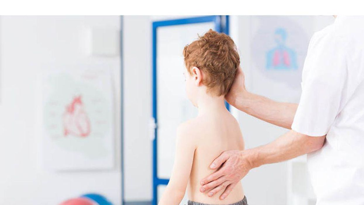 doctor checking girl for scoliosis