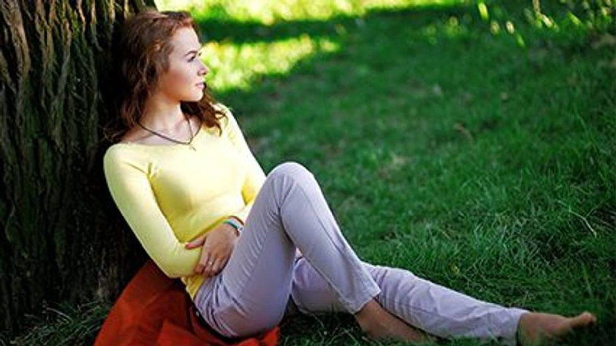 a girl sitting in the sun outdoors