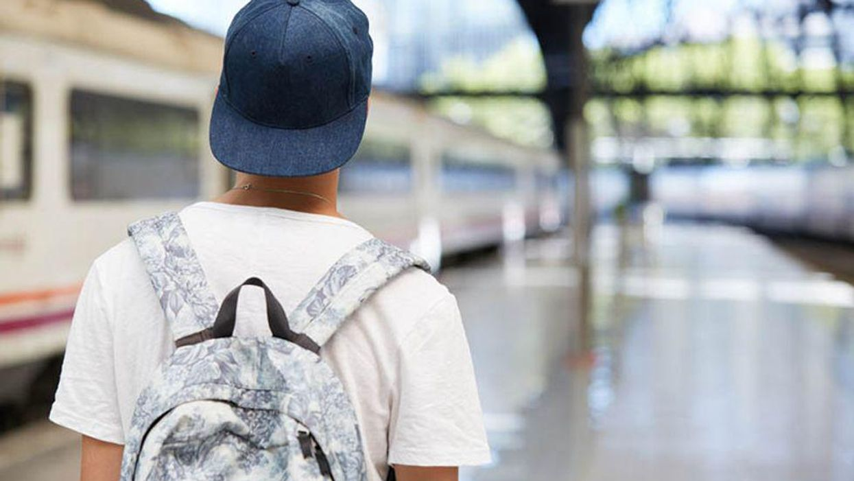 a back of a person with a backpack on the train station