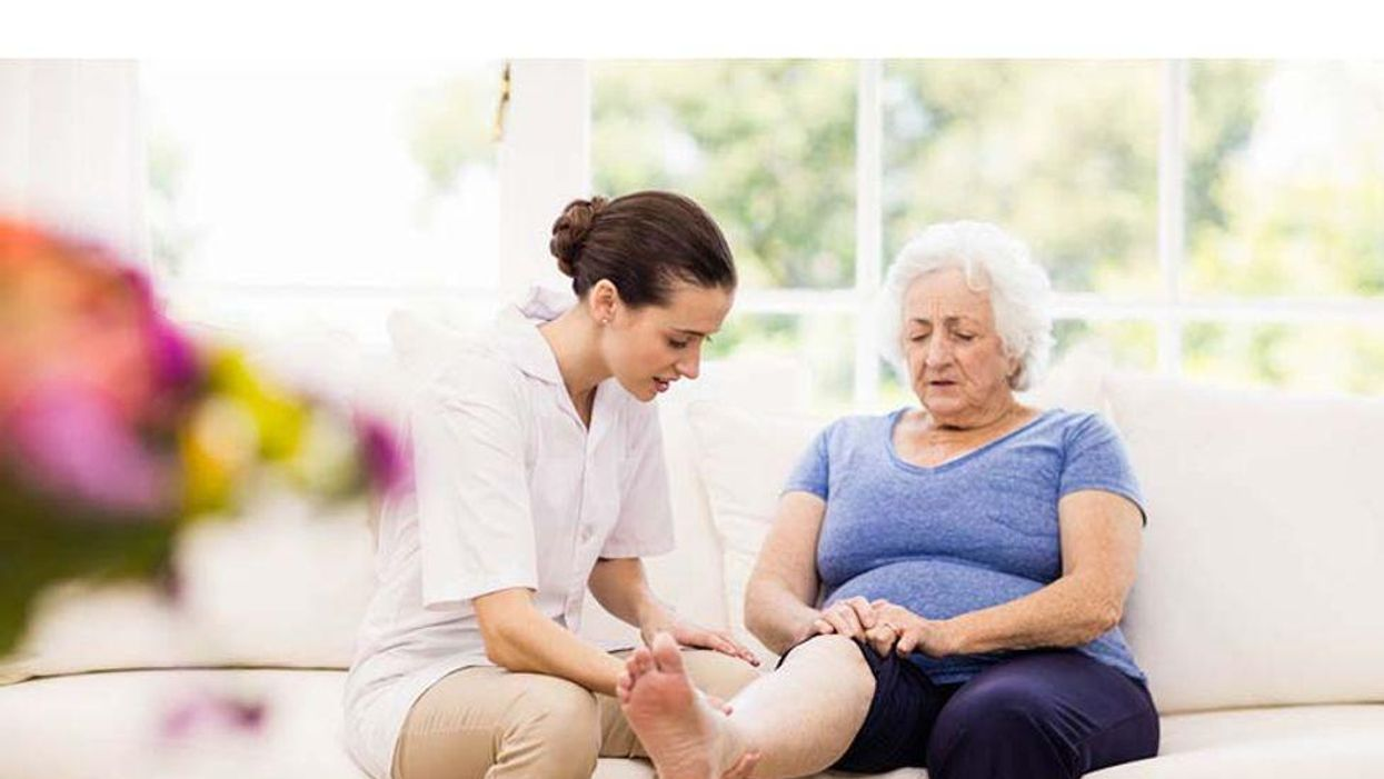 older woman showing her leg to a caregiver