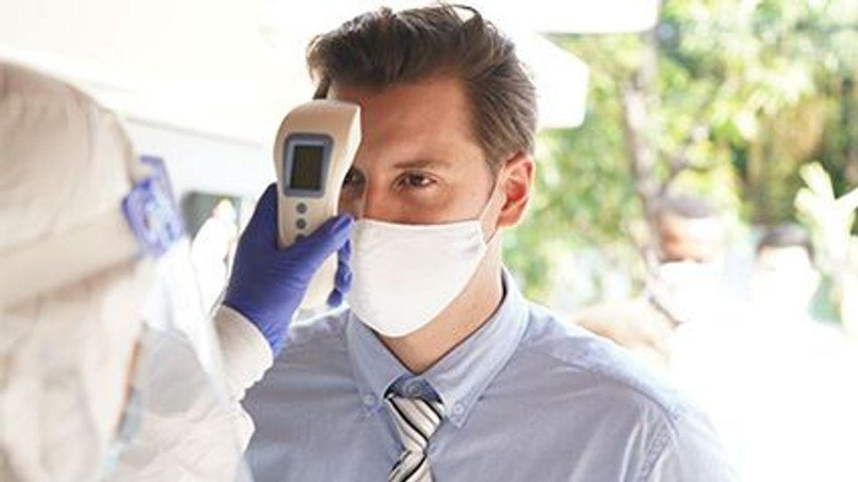 a person with a mask on being checked for his temperature