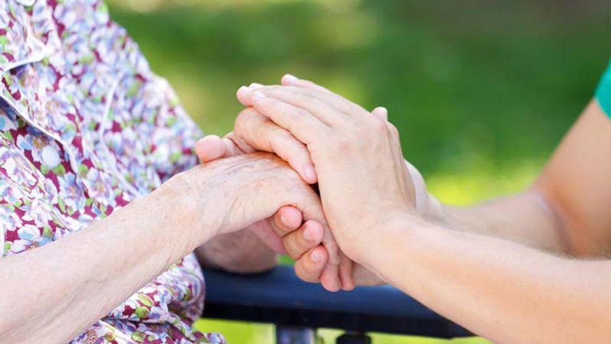 caregiver holding elderly person\'s hand
