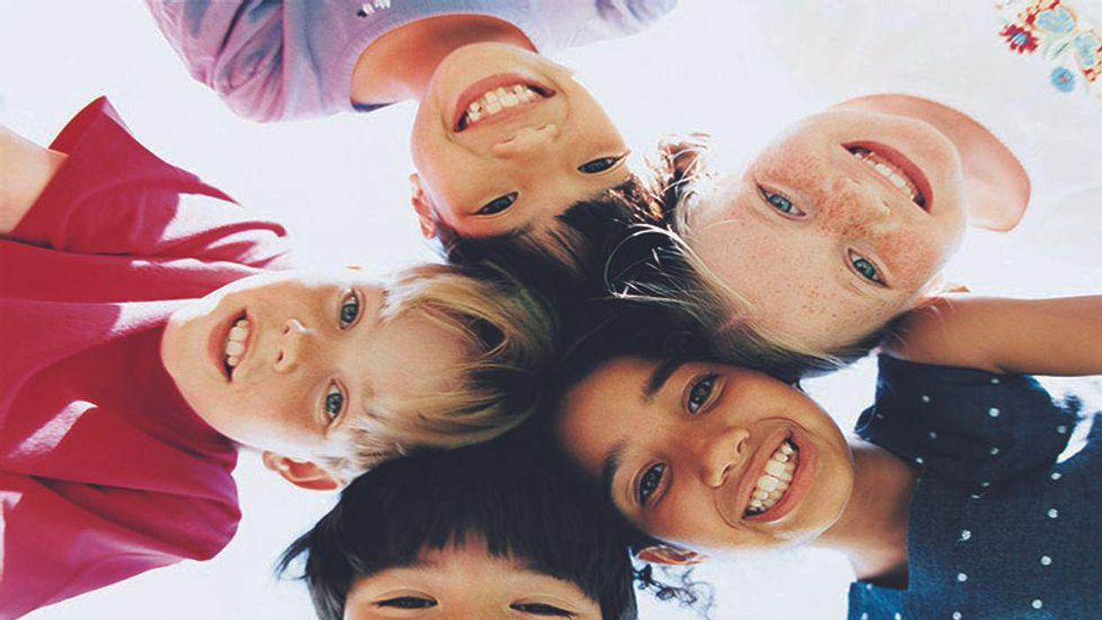 five kids smiling with their heads placed together