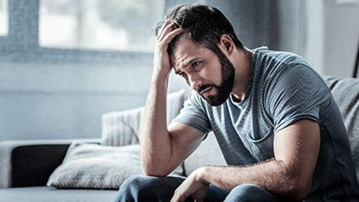 a man holding his head looking stressed