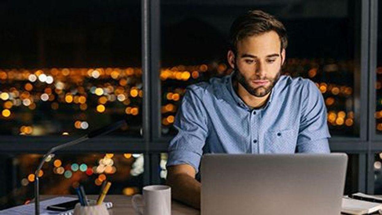 a man sitting at the computer late at night