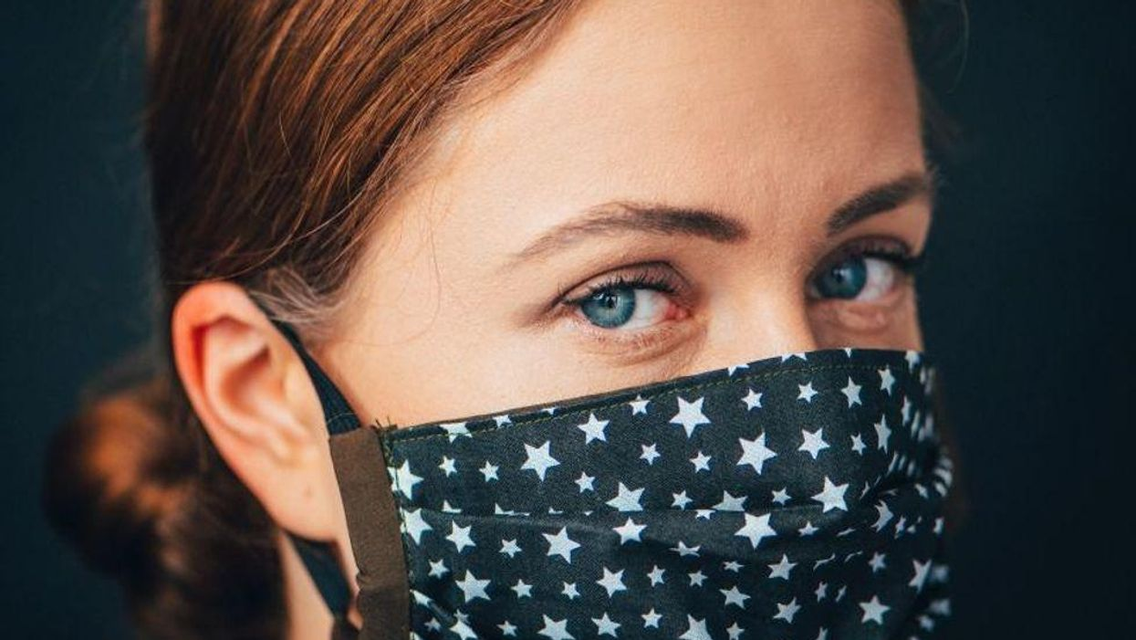 redhead woman wearing blue face mask with white stars