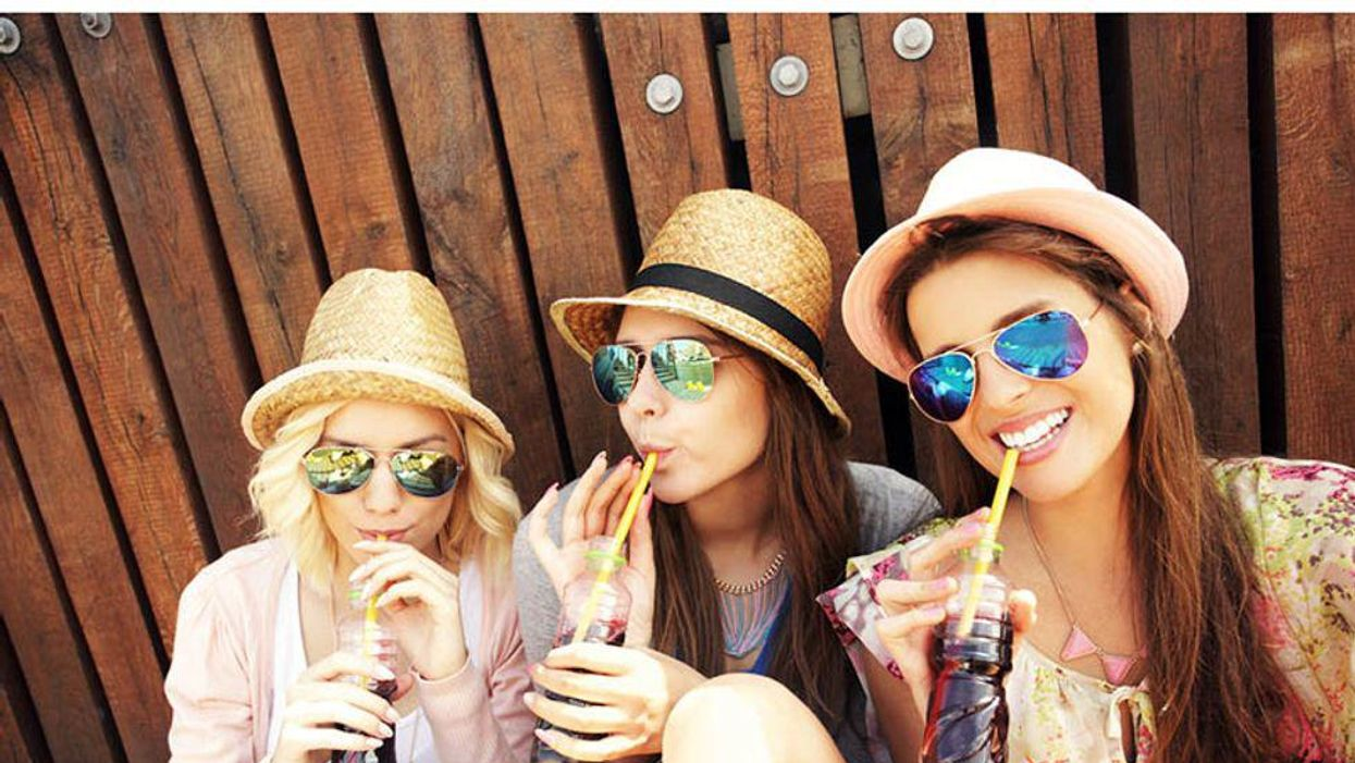 three girls in sunglasses drinking with the straw